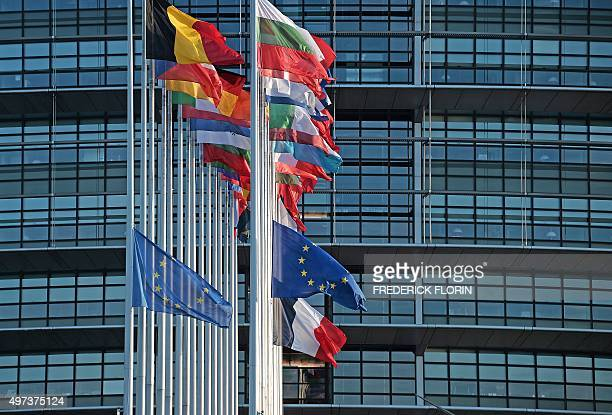 This photo taken on November 16 2015 shows the French and European Union flags flying at halfmast in front of the European Parliament building in...