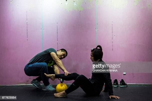 This photo taken on November 16 2017 shows MMA fighter Miao Jie getting assistance during a training session in Shanghai The 30yearold Shanghai...