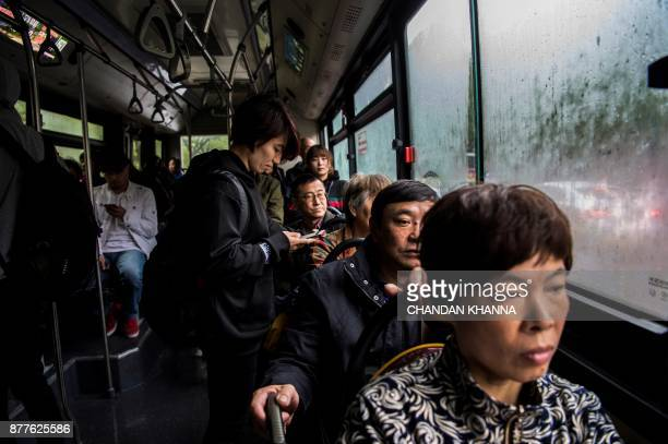 This photo taken on November 16 2017 shows MMA fighter Miao Jie looking at her phone as she takes a bus in Shanghai The 30yearold Shanghai native and...