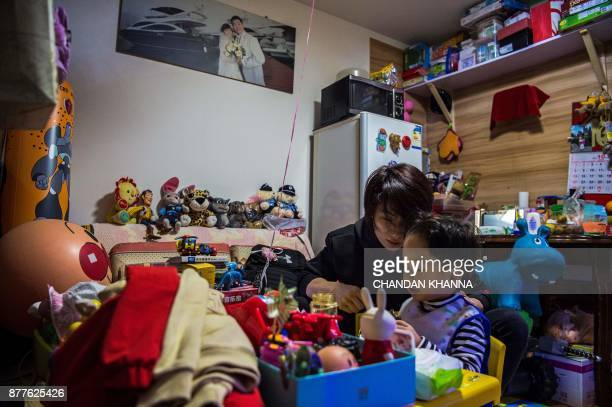 This photo taken on November 16 2017 shows MMA fighter Miao Jie making her threeyearold son Li Muyuan eat breakfast at their home in Shanghai The...