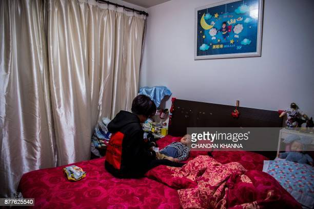 This photo taken on November 16 2017 shows MMA fighter Miao Jie getting her threeyearold son Li Muyuan up and ready for school at their house in...