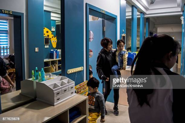 This photo taken on November 16 2017 shows MMA fighter Miao Jie dropping her threeyearold son Li Muyuan off at school in Shanghai The 30yearold...