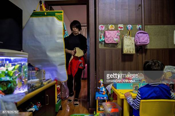 This photo taken on November 16 2017 shows MMA fighter Miao Jie helping her threeyearold son Li Muyuan get ready for school at their home in Shanghai...