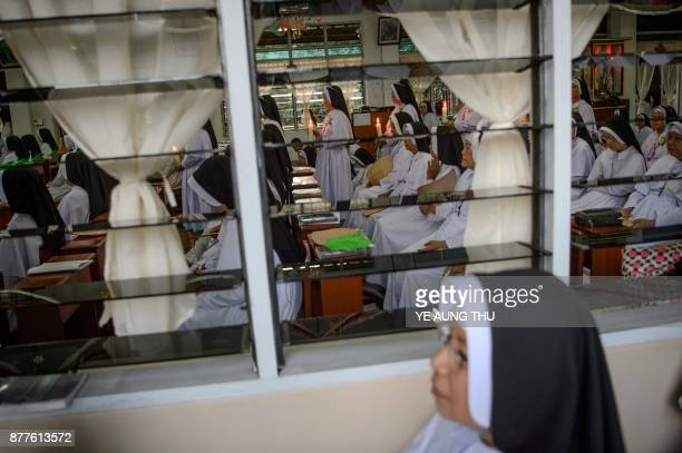 This photo taken on November 17 2017 shows nuns holding candles as they take part during a jubilee celebration marking the anniversary of when they...