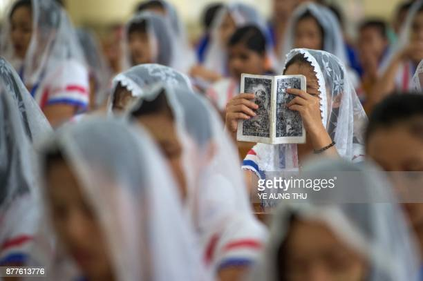 TOPSHOT This photo taken on November 19 2017 shows a Catholic devotee in a congregation holding up a prayer book during a Sunday service at the St...