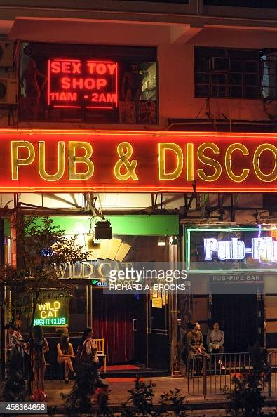 This photo taken on November 23 2013 shows employees sitting outside bars in the Wanchai district of Hong Kong AFP PHOTO / RICHARD A BROOKS