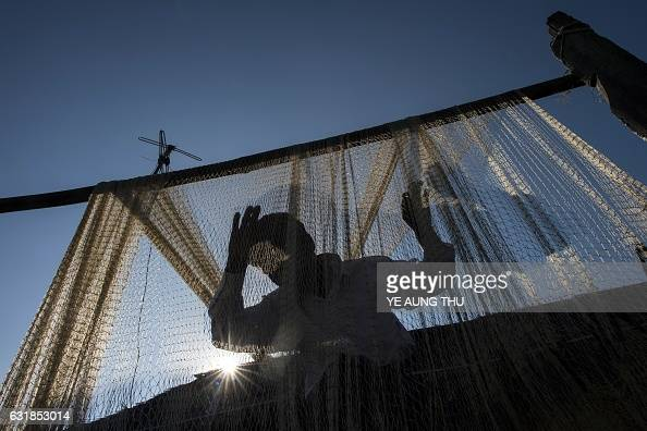 TOPSHOT This photo taken on November 23 2016 shows a fisherman cleaning his net near the Irrawaddy river in Mandalay Loved for generations for...