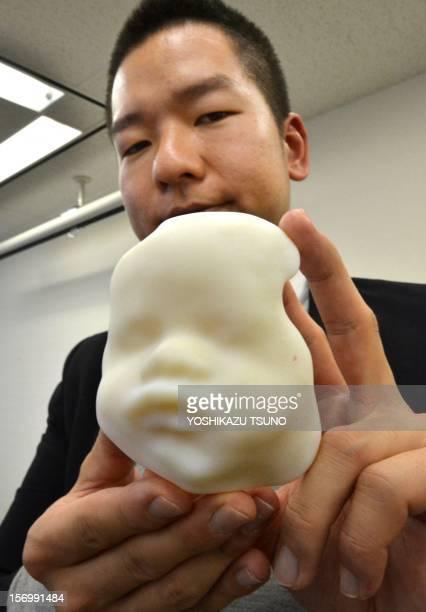 This photo taken on November 26 2012 shows Japan's 3D computeraided design venture Fasotec employee Tomohiro Kinoshita displaying a ninemonth fetal...