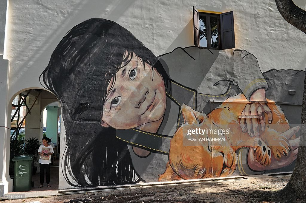 This photo taken on November 26, 2013 shows a woman (L) standing next to a mural painted on the wall of a private building by Lithuanian artist Ernest Zacharevic along Victoria Street in Singapore. The Lithuanian artist who angered Malaysian officials with a street mural depicting a knife-wielding Lego robber has found unlikely admirers across the border in graffiti-averse Singapore for his works on a softer theme.