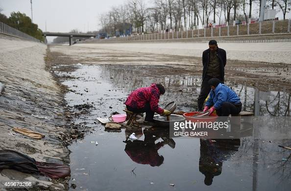 This photo taken on November 27 2014 shows Chinese women washing seeds in stagnant water in the bottom of a disused canal in Beijing Beijing has a...