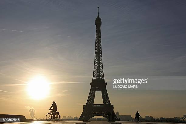 This photo taken on November 3 2016 in Paris shows a man riding a bicycle across the Trocadero Esplanade in front of the Eiffel Tower at sunrise /...