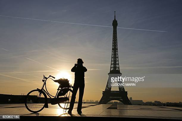 This photo taken on November 3 2016 in Paris shows a person taking a photo from the Trocadero Esplanade in front of the Eiffel Tower at sunrise / AFP...