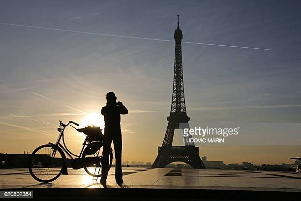 This photo taken on November 3 2016 in Paris shows a woman taking a photo from the Trocadero Esplanade in front of the Eiffel Tower at sunrise / AFP...