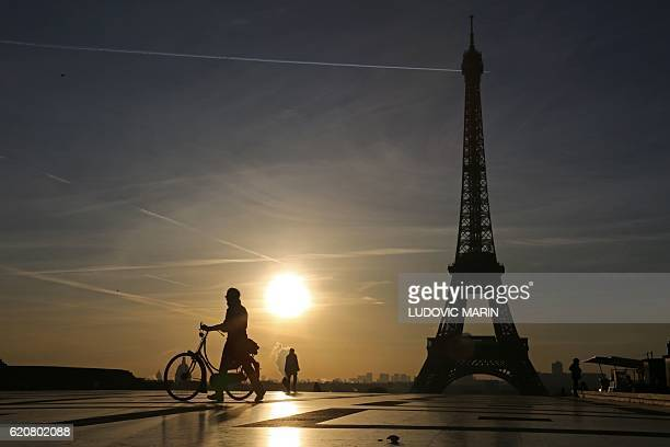 This photo taken on November 3 2016 in Paris shows people crossing the Trocadero Esplanade in front of the Eiffel Tower at sunrise / AFP / LUDOVIC...