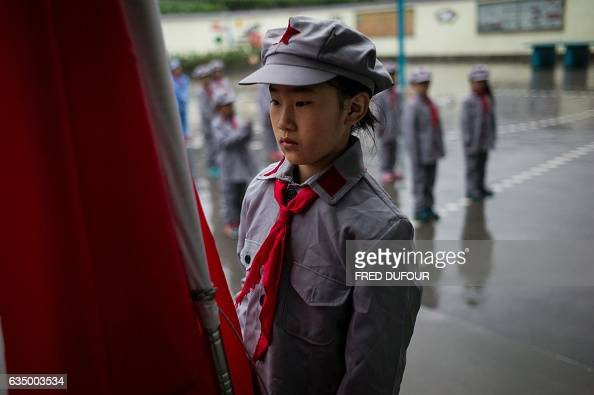 This photo taken on November 7 2016 shows students attending the flagraising ceremony at the Yang Dezhi 'Red Army' elementary school in Wenshui...