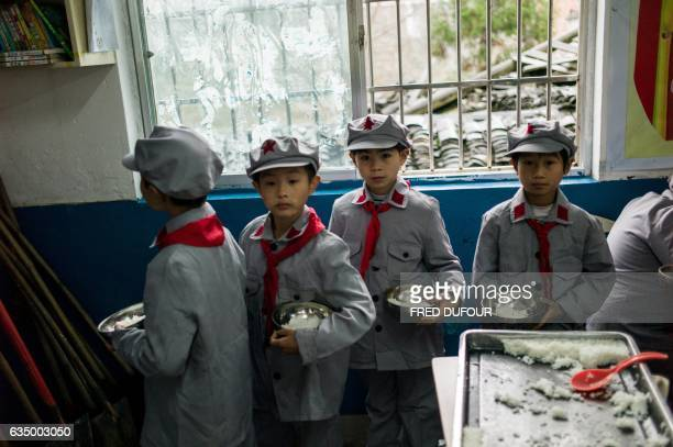 This photo taken on November 7 2016 shows students queueing for lunch in their classroom at the Yang Dezhi 'Red Army' elementary school in Wenshui...