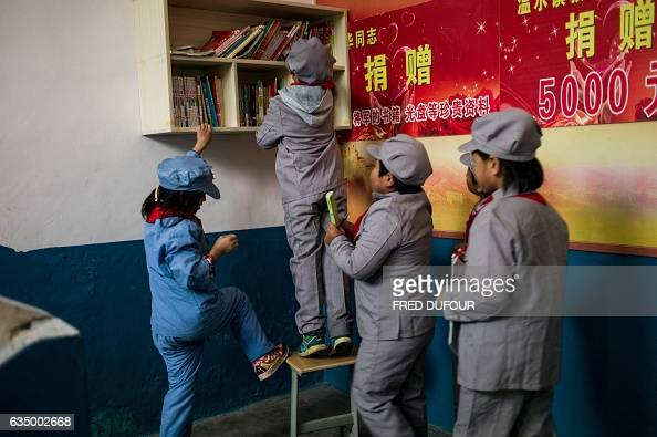 This photo taken on November 7 2016 shows students reaching for books at the Yang Dezhi 'Red Army' elementary school in Wenshui Xishui country in...