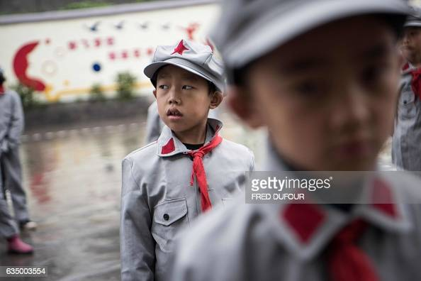 TOPSHOT This photo taken on November 7 2016 shows students taking part in the flagraising ceremony at the Yang Dezhi 'Red Army' elementary school in...