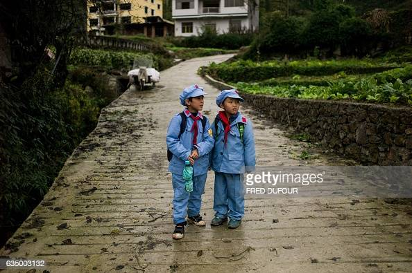 This photo taken on November 7 2016 shows students walking home from the Yang Dezhi 'Red Army' elementary school in Wenshui Xishui county in Guizhou...