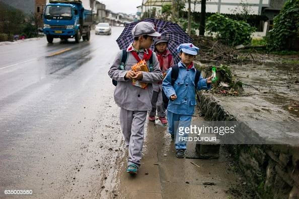 TOPSHOT This photo taken on November 7 2016 shows students walking home from the Yang Dezhi 'Red Army' elementary school in Wenshui Xishui county in...