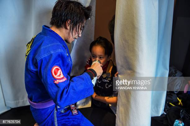 This photo taken on November 7 2017 shows MMA fighter Miao Jie giving her threeyearold son Li Muyuan a drink during a training session in Shanghai...