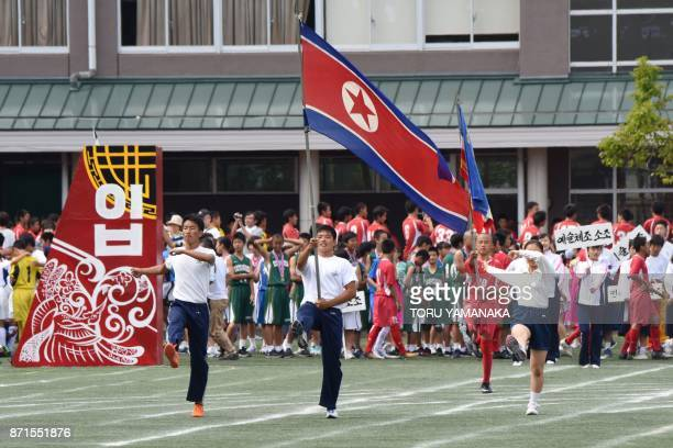 This photo taken on October 1 2017 shows students of the Tokyo Korean Junior and Senior High School marching as the North Korean national flag is...