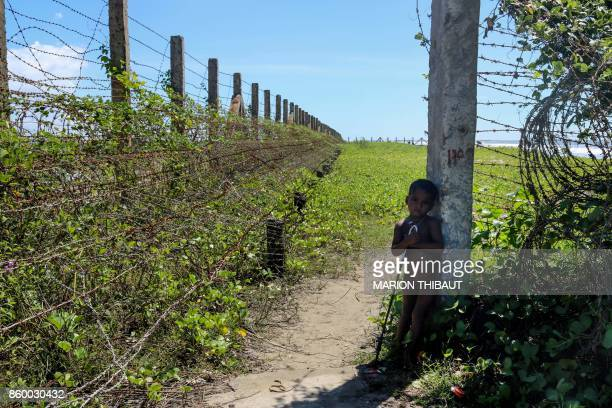 TOPSHOT This photo taken on October 10 2017 shows a child stand next to a barbed wire fence along the MyanmarBangladesh border near the Du Thar Ya...