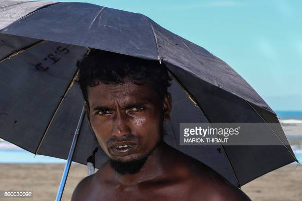 This photo taken on October 10 2017 shows a man holding an umbrella as he waits to cross the border to Bangladesh at the bank of Ah Lae Than Kyaw...