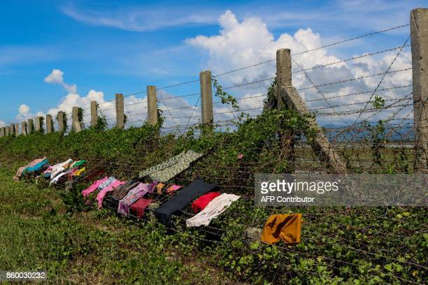 This photo taken on October 10 2017 shows clothes being dried on a barbed wire fence along the MyanmarBangladesh border near the Du Thar Ya village...