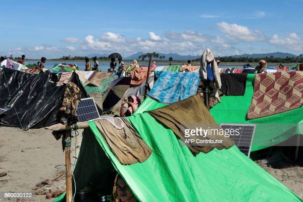 This photo taken on October 10 2017 shows people gathering as they wait to cross the border to Bangladesh at the bank of Ah Lae Than Kyaw village in...