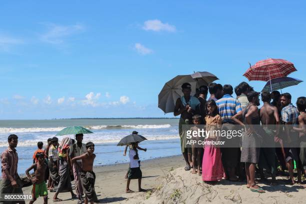 This photo taken on October 10 2017 shows people waits for cross the border to Bangladesh at the bank of Gaw Du Thar Ya village in Maungdaw Northern...
