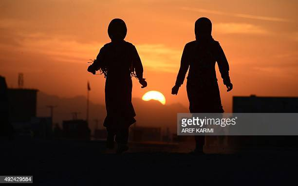 This photo taken on October 12 2015 shows Afghan refugee girls walking outside tents on the outskirts of Herat AFP PHOTO / Aref Karimi