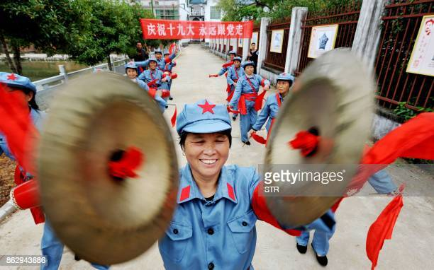 TOPSHOT This photo taken on October 18 2017 shows people dressed in Red Army uniforms performing to celebrate the opening of the 19th Party Congress...