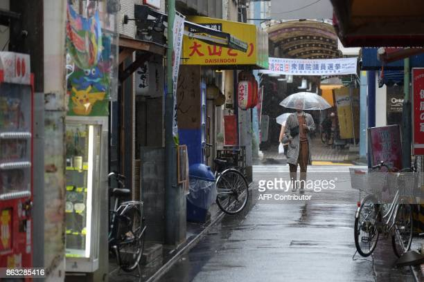 This photo taken on October 19 2017 shows a pedestrian walking past a banner encouraging participation in the upcoming October 22 general election in...