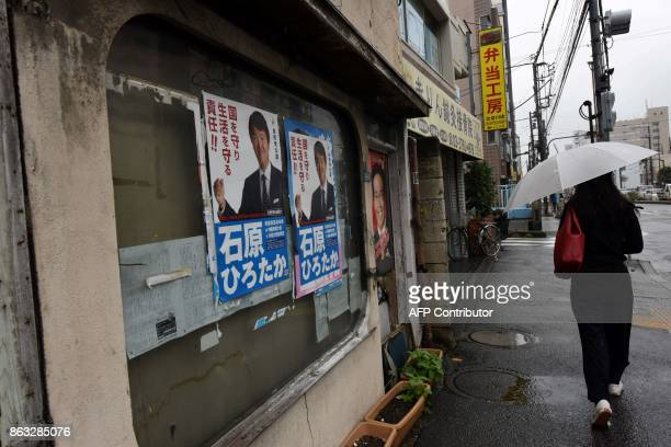 This photo taken on October 19 2017 shows a pedestrian walking past elections campaign posters displayed on windows of a house in a shopping area in...