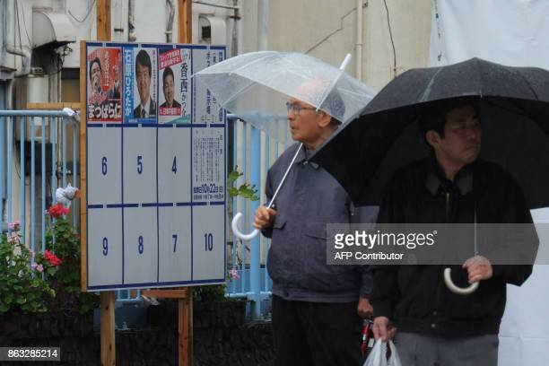 This photo taken on October 19 2017 shows pedestrians standing in front of an election poster bulletin board for the upcoming October 22 general...