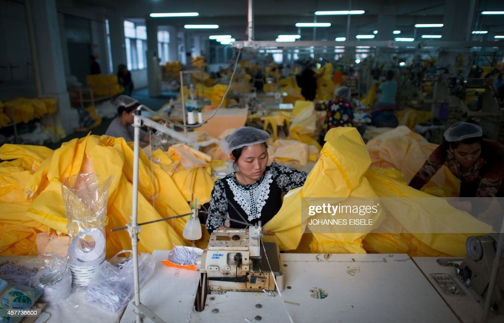 This photo taken on October 23 2014 in Anqiu some 500 kilometers south of Bejing shows women working on the CT1SL428 a protective suit for use in...