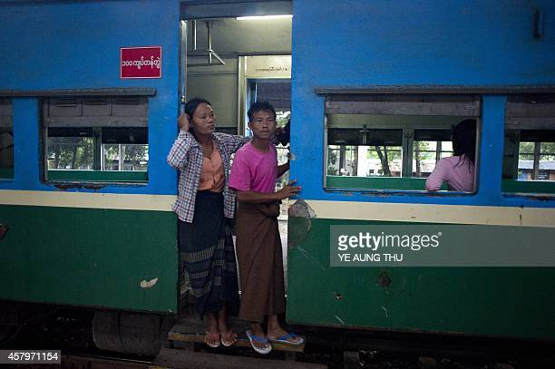 This photo taken on October 26 2014 show people hanging out of a train in Yangon Landmark elections in Myanmar that could propel opposition leader...