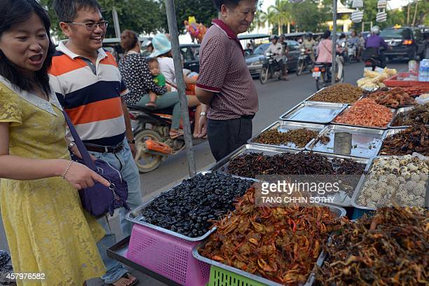 This photo taken on October 26 2014 shows tourists smiling as they look at insects displayed for sale along a street in Phnom Penh AFP PHOTO/ TANG...