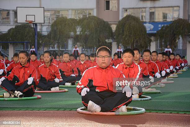 This photo taken on October 27 2015 shows pupils exercising on the playground during a break at an elementary school in Jilin northeast China's Jilin...