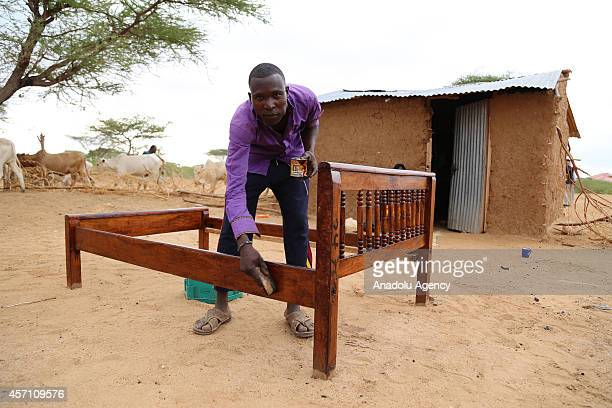 This photo taken on October 4 2014 shows a refugee man posing while he polishes a bedstead at Dadaab refugee camp in Kenya the largest refugee...