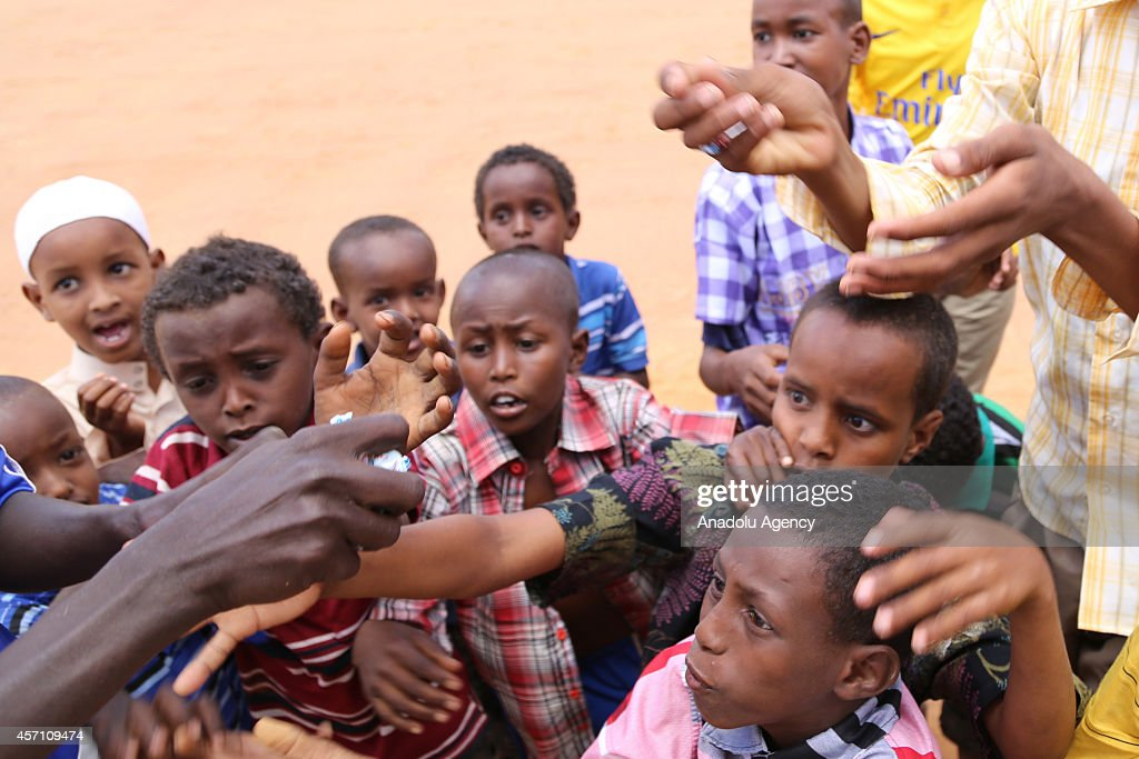 This photo taken on October 4 2014 shows refugee children reaching out for candies distributed by an African man at Dadaab refugee camp in Kenya the...