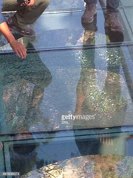 This photo taken on October 5 2015 shows people standing by a cracked glass tile on a glassbottomed walkway in Yuntaishan in Jiaozuo central China's...