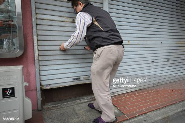 This photo taken on October 6 2017 shows a shopowner opening the shutters of his store at a shopping area in Tokyo On the face of it the Japanese...