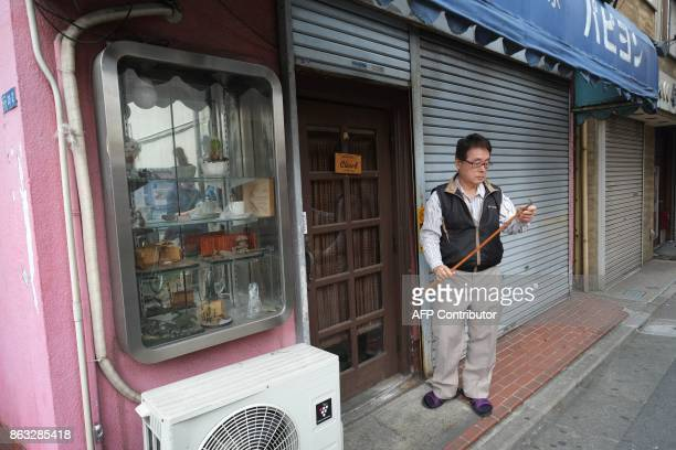 This photo taken on October 6 2017 shows a shopowner standing outside his closed shop at a shopping area in Tokyo On the face of it the Japanese...