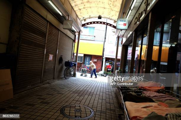 This photo taken on October 6 2017 shows a woman walking past shuttered stores in a shopping area in Tokyo On the face of it the Japanese economy is...