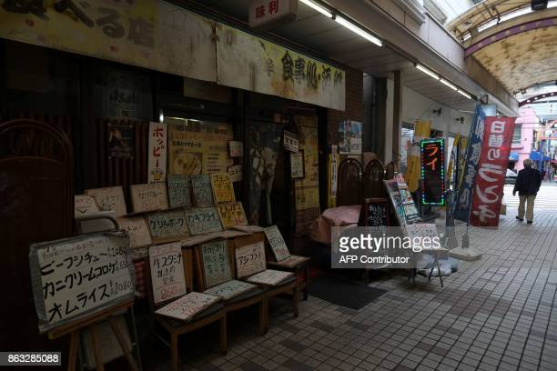 This photo taken on October 6 2017 shows menus for various meals displayed at the entrance of a dining room in a shopping area in Tokyo On the face...