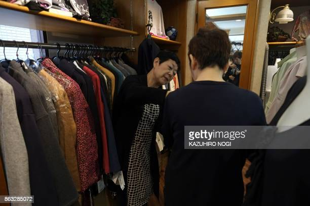 This photo taken on October 6 2017 shows Michiko Hachiman serving a customer in her clothes shop at a shopping area in Tokyo On the face of it the...