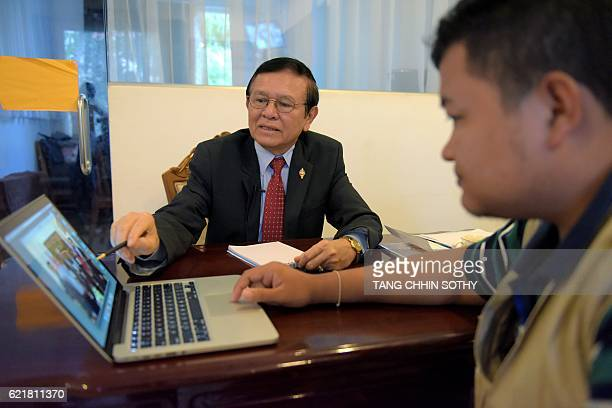 This photo taken on October 7 2016 shows Cambodia's opposition party deputy leader Kem Sokha giving advice to a member of his Facebook team at his...
