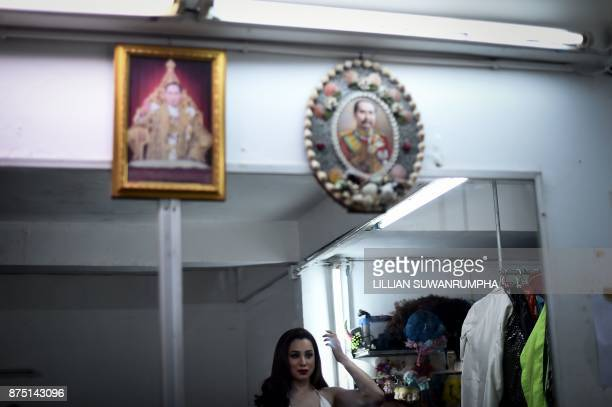 This photo taken on October 7 2017 shows a cabaret performer checking her appearance in front of portraits of Thai king Bhumibol Adulyadej and Thai...